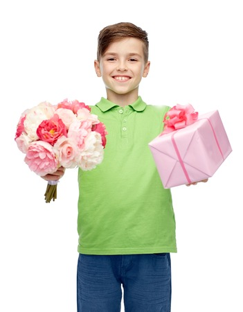 pre teen boy: childhood, holidays, presents and people concept - happy boy holding flower bunch and gift box Stock Photo