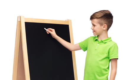 pre adolescent boys: childhood, education, school, advertisement and people concept - happy smiling boy in green polo t-shirt with chalk and blank school blackboard Stock Photo