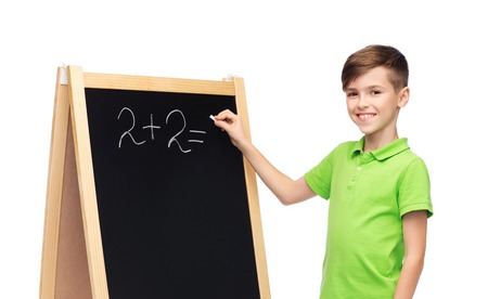 pre teen boys: childhood, education, school, advertisement and people concept - happy smiling boy in green polo t-shirt solving math task on blank school chalk blackboard