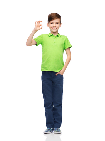 pre adolescent boys: childhood, fashion, advertisement and people concept - happy boy in white t-shirt and jeans showing ok hand sign