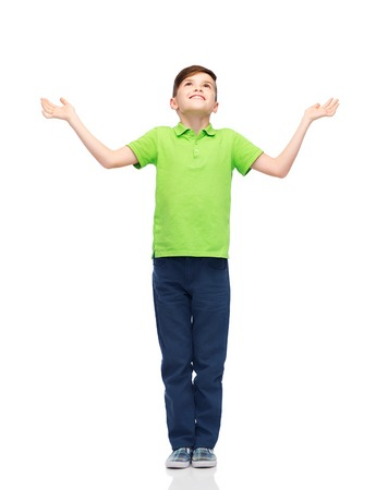 gladness: childhood, achievement, gladness and people concept - happy smiling boy in green polo t-shirt raising hands and looking up Stock Photo