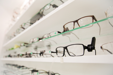 optics, health care and vision concept - close up of eyeglasses at optician Stock Photo