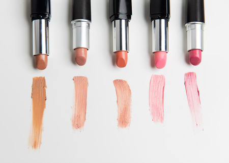 up view: cosmetics, makeup and beauty concept - close up of lipsticks range