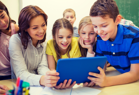 elementary: education, elementary school, learning, technology and people concept - group of school kids with teacher looking to tablet pc computer in classroom