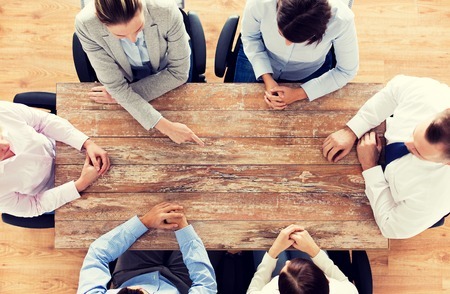 discussion: business, people and team work concept - close up of creative team sitting at table and pointing finger to something in office