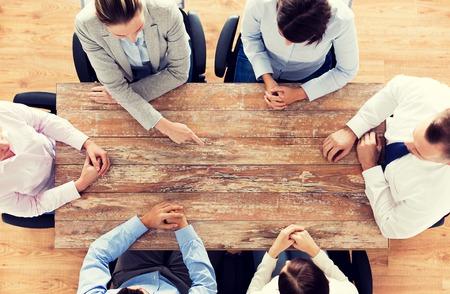 het bedrijfsleven, mensen en teamwork concept - close-up van het creatieve team zitten aan tafel en wijzende vinger op iets in het kantoor Stockfoto