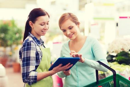 사람, 원 예, 쇼핑, 판매 및 소비 개념 - 태블릿 pc와 행복 정원사 온실에서 꽃을 선택하는 여자를 돕는