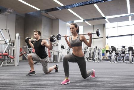 Sport, Bodybuilding, Lifestyle und Menschen Konzept - junger Mann und Frau mit Hantel beugen Muskeln und macht Schulter drücken Longe im Fitness-Studio Standard-Bild