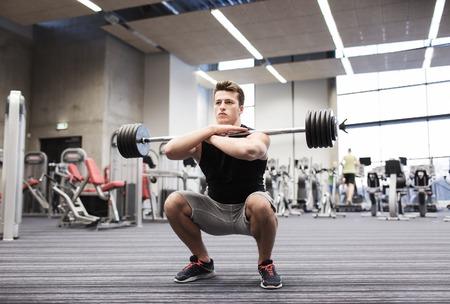 Sport, Bodybuilding, Lifestyle und Menschen Konzept - junger Mann mit Langhantel Kniebeugen in der Turnhalle