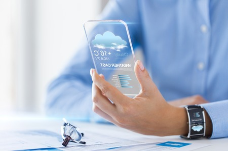 cloud technology: technology, application, weather, forecast and people concept - close up of woman hand holding transparent smartphone with cloud icon and air temperature on screen at office