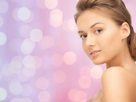 pretty young girl: people, beauty and body care concept - lovely woman face over pink lights background