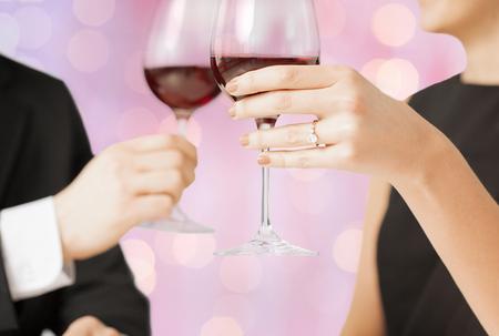 matrimonio feliz: las personas, las vacaciones, el matrimonio y el concepto de la celebración - felices dedicadas copas tintinean de los pares durante las vacaciones fondo de las luces