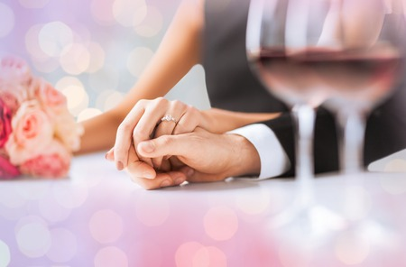 people, holidays, engagement and love concept - engaged couple holding hands with diamond ring over holidays lights background