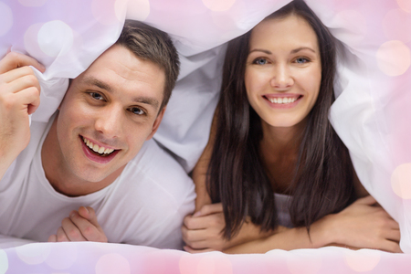 hispanic family: love, valentines day and people concept - happy couple in bed over holidays lights background
