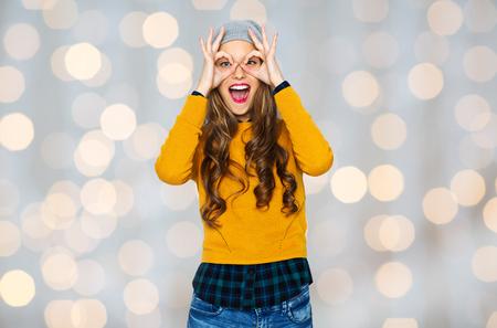 Menschen, Stil und Mode-Konzept - glückliche junge Frau oder Teenager-Mädchen in Freizeitkleidung und Hipster-Hut, die Spaß über Urlaub Lichter Hintergrund Standard-Bild