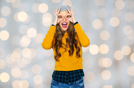 people, style and fashion concept - happy young woman or teen girl in casual clothes and hipster hat having fun over holidays lights background