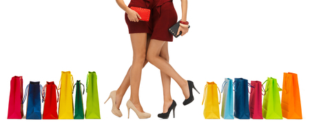 clutches: people, sale and consumerism concept - close up of two women in red dresses and high heel shoes with clutches and shopping bags