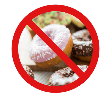 fattening: fast food, low carb diet, fattening and unhealthy eating concept - close up of glazed donuts behind no symbol or circle-backslash prohibition sign Stock Photo