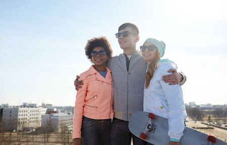 multiracial family: tourism, travel, people, leisure and teenage concept - group of happy friends in sunglasses hugging and talking on city street