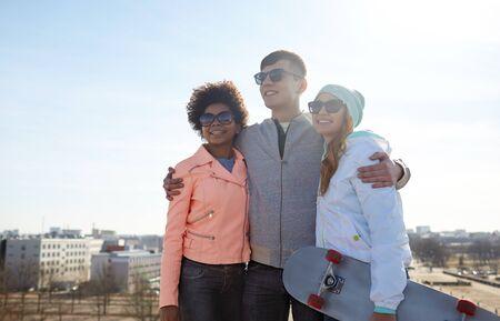 familia abrazo: turismo, viaje, gente, ocio y concepto de adolescente - grupo de amigos felices en gafas de sol que abrazan y que hablan en calle de la ciudad