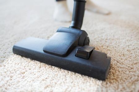 mujer limpiando: las personas, el trabajo dom�stico y de limpieza concepto - cerca de aspirador de alfombras limpieza de la boquilla en el hogar Foto de archivo