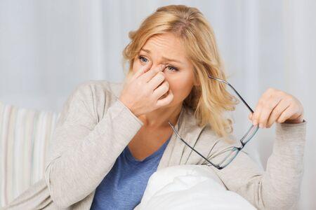 les gens, la santé, la vue, le stress et le concept de problème - femme fatiguée de prendre des lunettes off à la maison