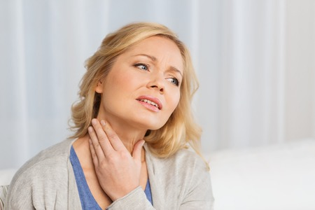 people, healthcare and problem concept - unhappy woman touching her neck and suffering from throat pain at home Stock Photo