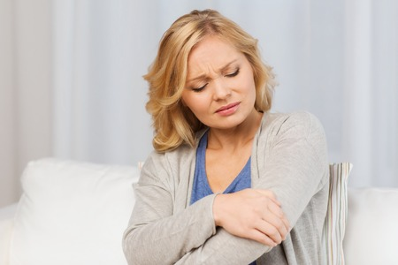 female elbow: people, healthcare and problem concept - unhappy woman suffering from pain in hand at home Stock Photo