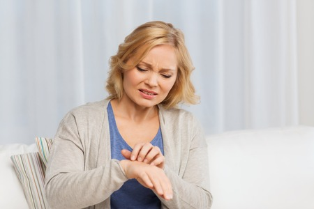 unhappy people: people, healthcare, dermatology, allergy and health problem concept - unhappy woman suffering from hand inch at home