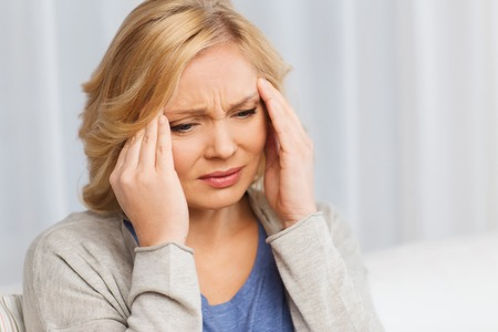 unhappy people: people, healthcare, stress and problem concept - unhappy woman suffering from headache at home