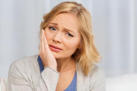 mensen, gezondheidszorg, tandheelkunde en probleemoplossend concept - ongelukkige vrouw lijdt kiespijn thuis Stockfoto