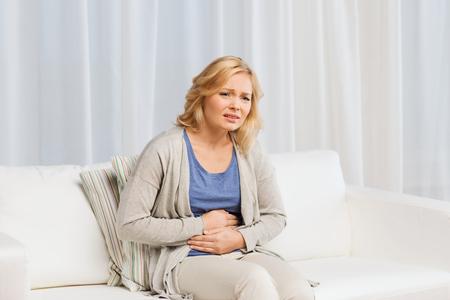 Mensen, gezondheidszorg en probleemconcept - ongelukkige vrouw die thuis lijdt aan buikpijn Stockfoto
