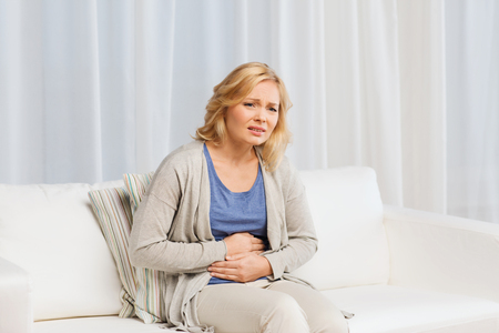 people, healthcare and problem concept - unhappy woman suffering from stomach ache at home