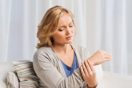 las personas, la salud y el concepto de problema - infeliz mujer que sufre de dolor en la mano en el hogar Foto de archivo