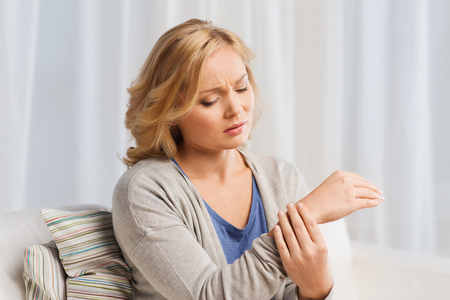 people, healthcare and problem concept - unhappy woman suffering from pain in hand at home Stock Photo
