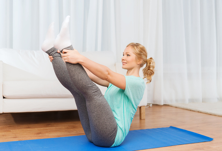 work at home: fitness, sport, people and healthy lifestyle concept - woman exercising on mat at home Stock Photo