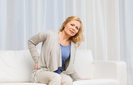 Les gens, la santé et le concept de problème - malheureuse femme souffrant de douleurs au dos ou rênes à la maison Banque d'images - 52256807