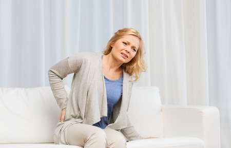 reins: people, healthcare and problem concept - unhappy woman suffering from pain in back or reins at home Stock Photo