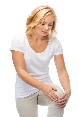 mensen, gezondheidszorg en probleemconcept - ongelukkige vrouw die aan pijn in been lijden Stockfoto