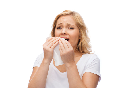 people, healthcare, rhinitis, cold and allergy concept - unhappy woman with paper napkin sneezing