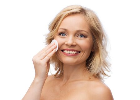 swab: beauty, people and skincare concept - young woman cleaning face and removing make up with cotton pad Stock Photo