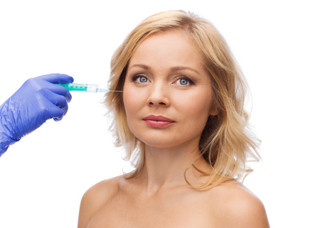antiaging: beauty, anti-aging cosmetic surgery concept - woman face and beautician hand in glove with syringe making injection to cheek Stock Photo