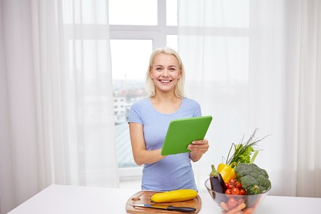 food technology: healthy eating, cooking, vegetarian food, technology and people concept - smiling young woman with tablet pc computer and bowl of vegetables at home Stock Photo