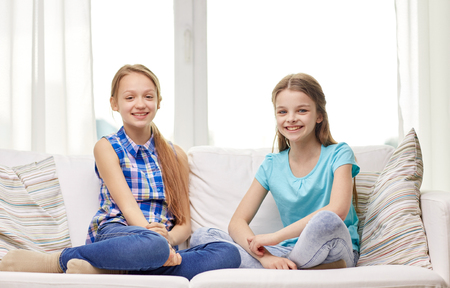 people, children, friends and friendship concept - happy little girls sitting on sofa at home Stock Photo