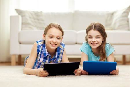 two children: people, children, technology, friends and friendship concept - happy little girls with tablet pc computers lying on floor at home