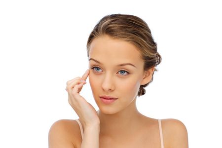 eye cream: beauty, people, cosmetics, skincare and health concept - young woman applying cream to her face