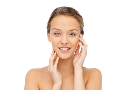 beauty, people and health concept - smiling young woman with bare shoulders touching her face
