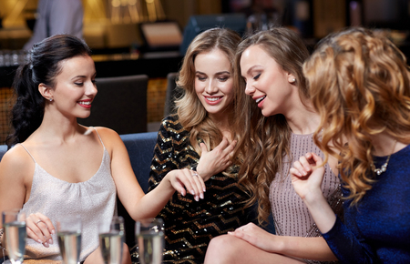out of engagement: celebration, friends, bachelorette party and holidays concept - happy woman showing engagement ring to her friends with champagne glasses at night club Stock Photo