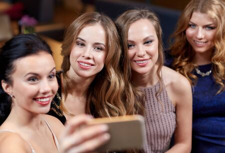 party people: celebration, friends, bachelorette party, technology and holidays concept - happy women with smartphone taking selfie at night club Stock Photo