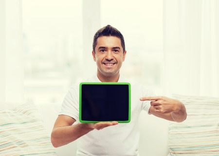 mid distance: technology, people and lifestyle, distance learning concept - happy man showing tablet pc computer black blank screen at home